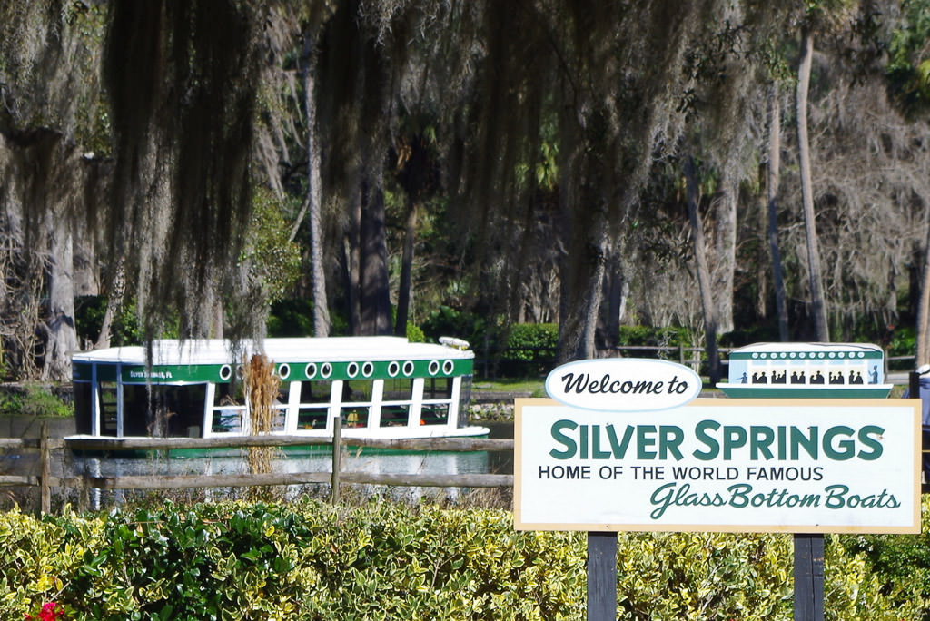 Sign for Silver Springs with Glass Bottom Boat on the water in the background.