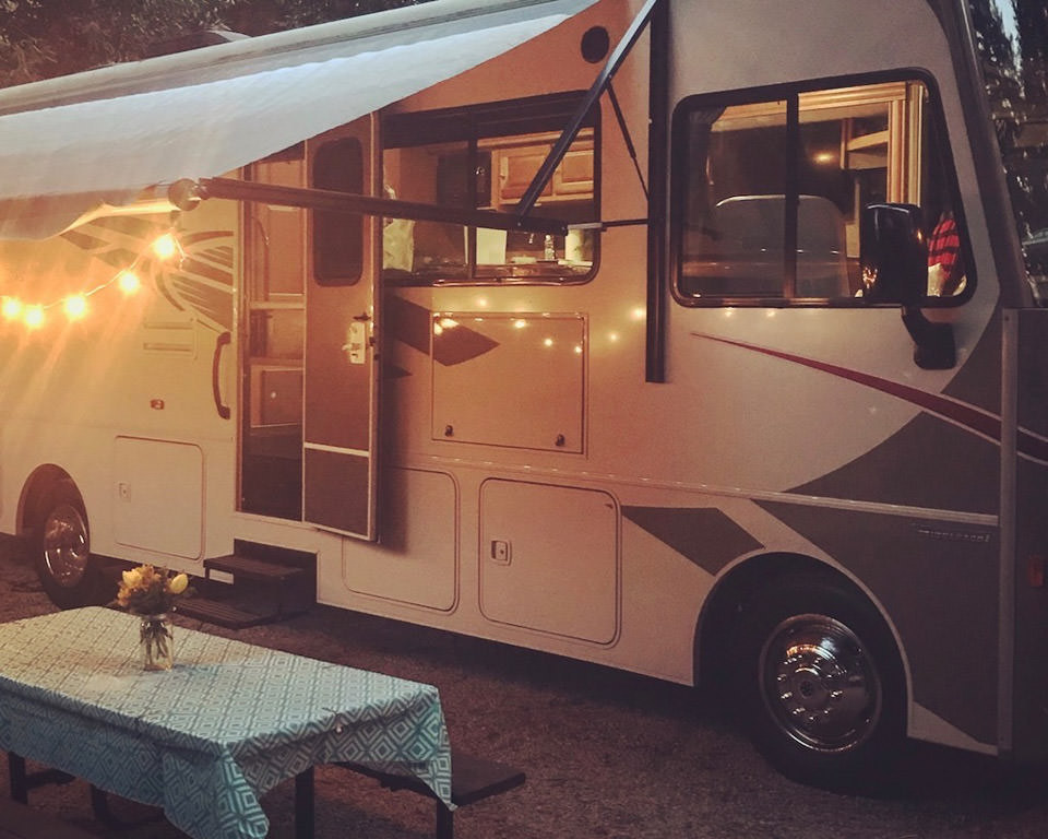Winnebago with awning out with lights strung underneath and a picnic table with flowers on it.