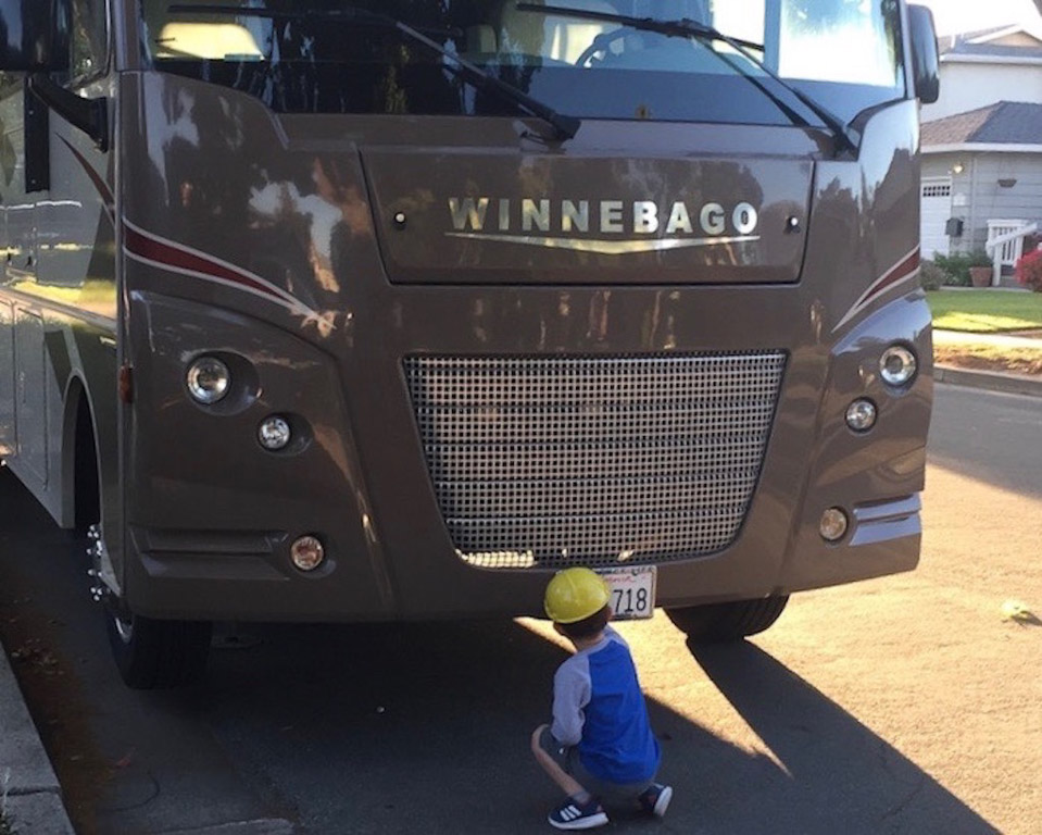 Child kneeling in front of a Winnebago by the front license plate.