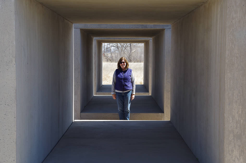 Woman posing in the concrete cube art.