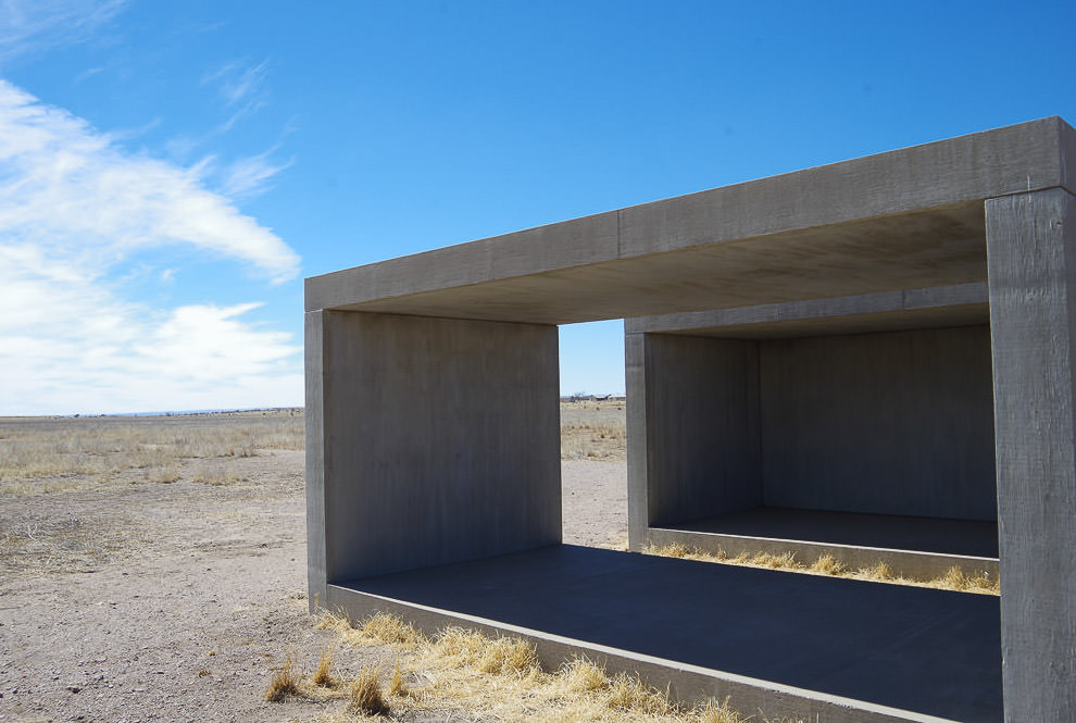 Concrete cube art in the middle of a gravel field.