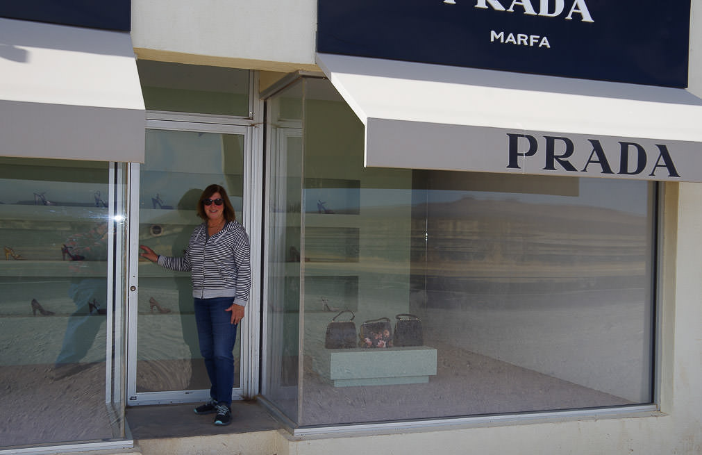 Woman in front of Prada store.