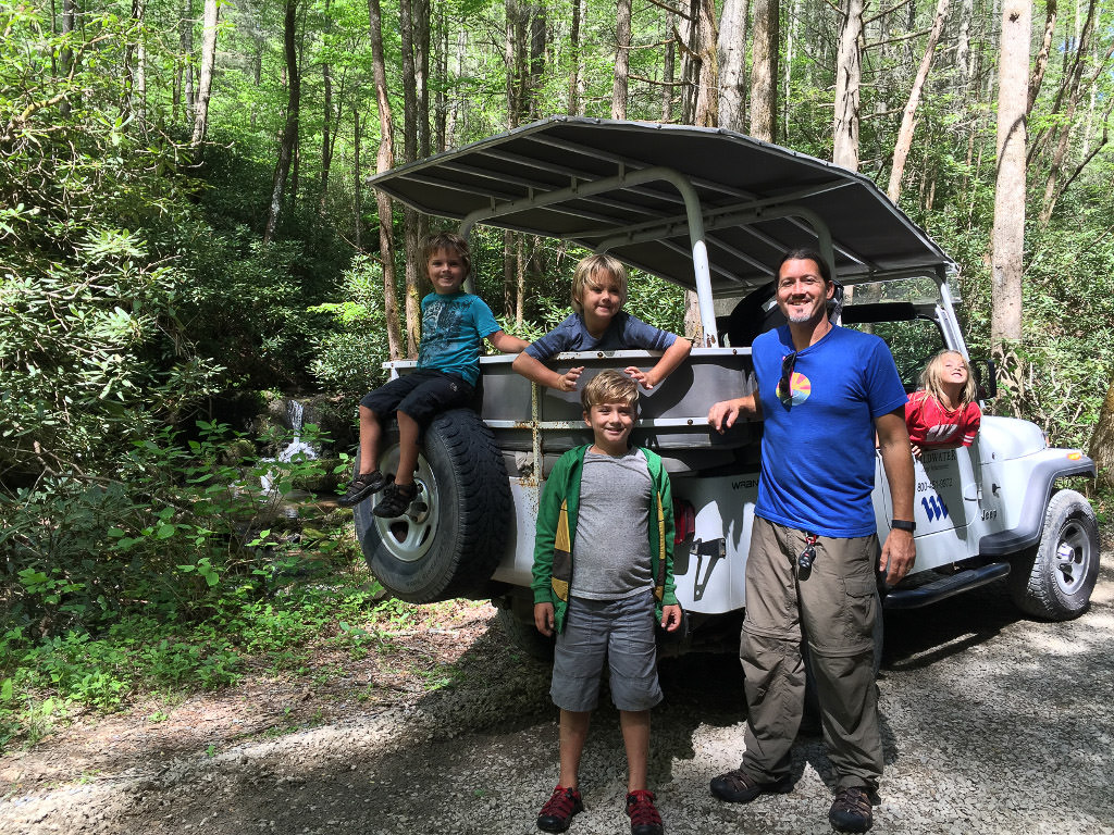 Family posing on a jeep in the middle of the woods on the Wildwater Pigeon Jeep Tour.
