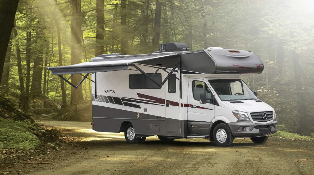 Winnebago Vita with awning out on a dirt road in the woods.
