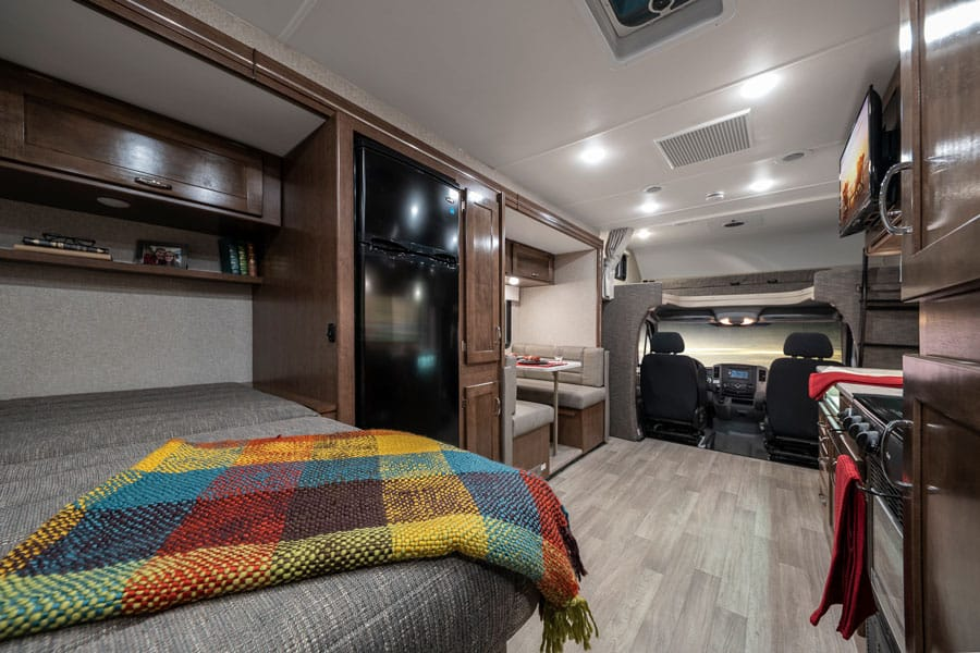 Winnebago Vita interior with bed, dinette nook, kitchenette and front cab.