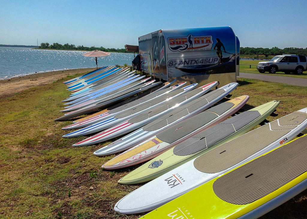 Stand up paddle boards lined up along lake