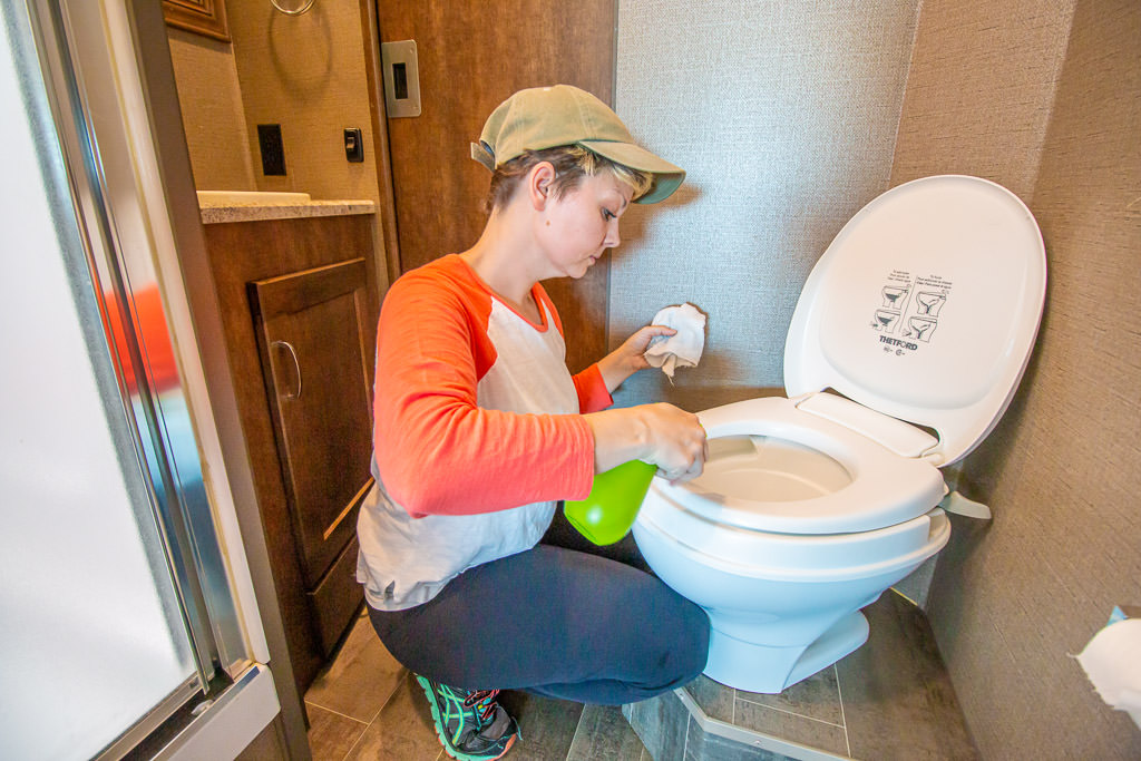 Young woman scrubs down the RV toilet for spring cleaning