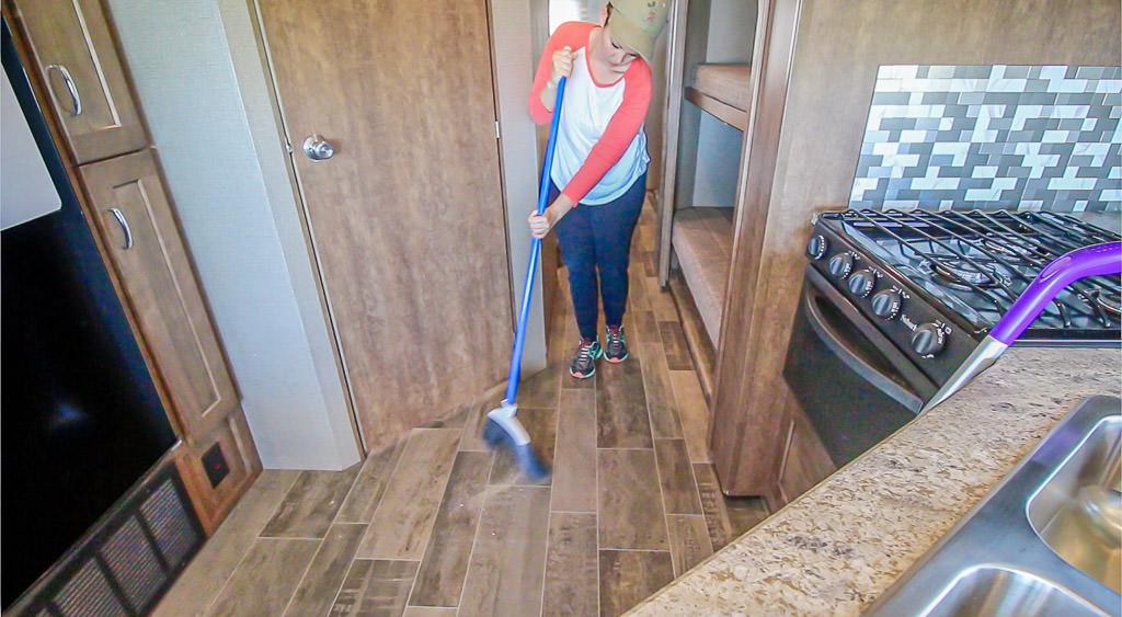 Young woman sweeps floor of Winnebago Intent for spring cleaning