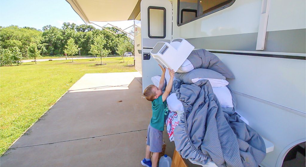 Young boy removes items from the RV for RV spring cleaning