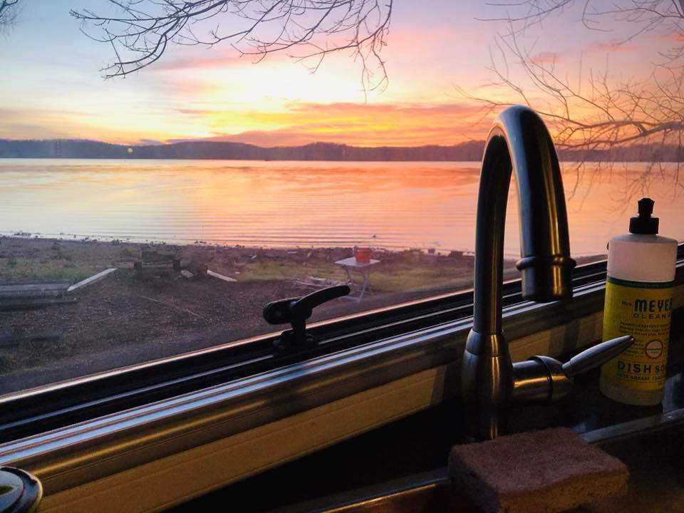 Kitchen sink with colorful sunset over hills out the window.