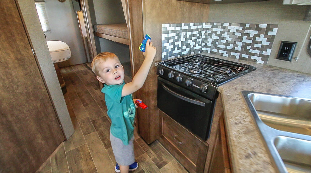 Young man helps with RV spring cleaning using water squirt guns
