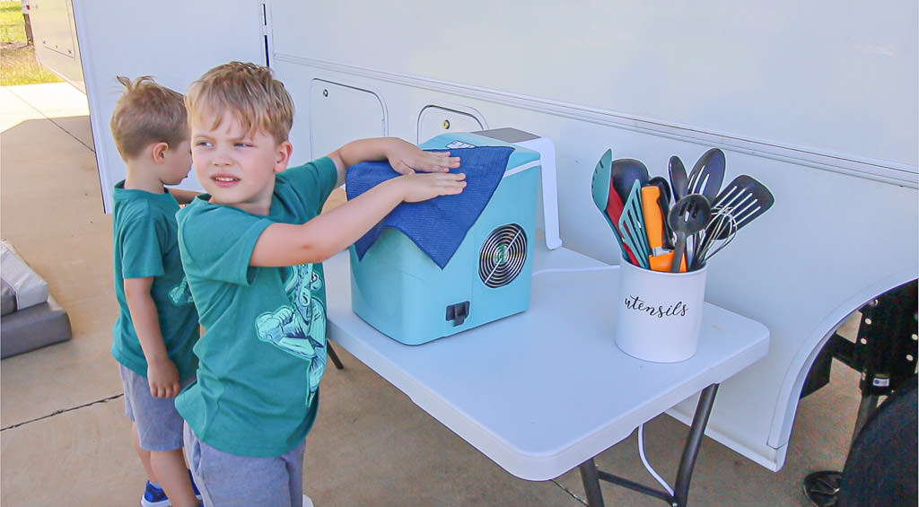 Young boys help with RV spring cleaning and wipe down household accessories