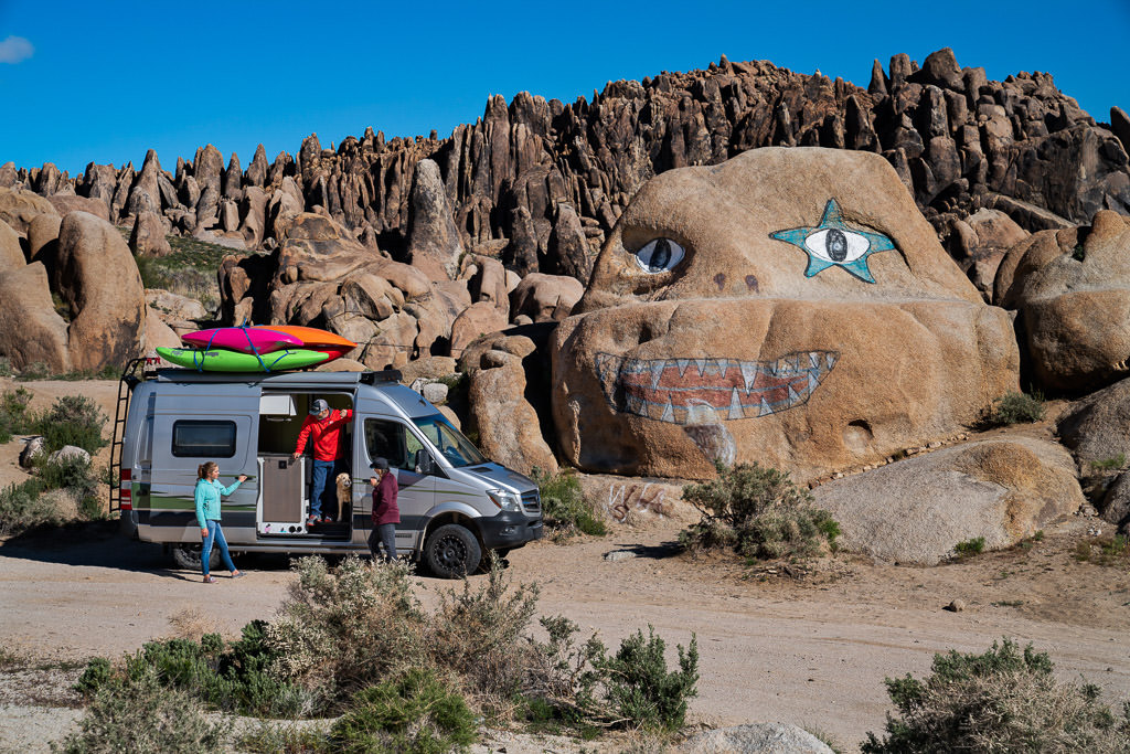 Family coming out of Winnebago Revel that is parked next to unique rock formation that has a face painted on one of the big rocks.