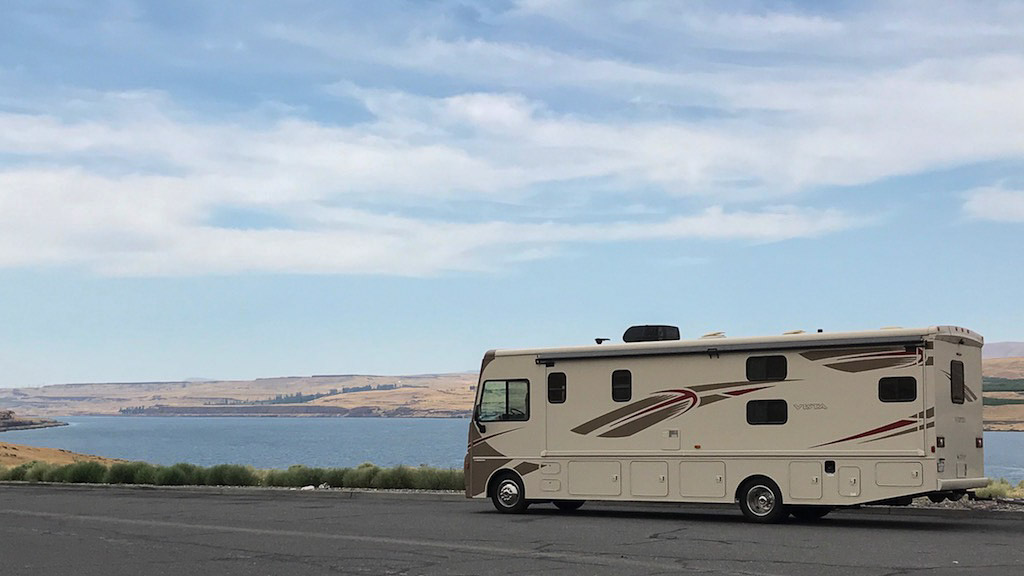 Winnebago Vista parked on the side of the road next to body of water.