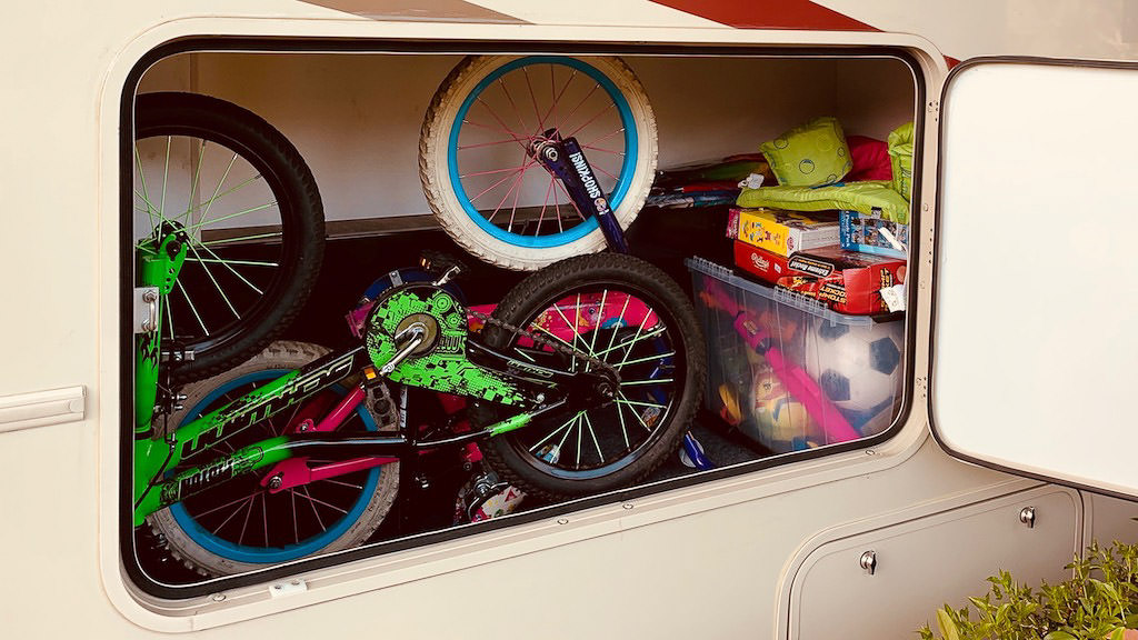 Bikes and games in outside storage compartment of the Winnebago Vista.