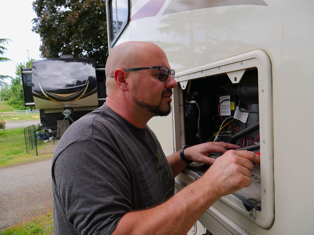A man evaluating electrical components of his Winnebago Vista