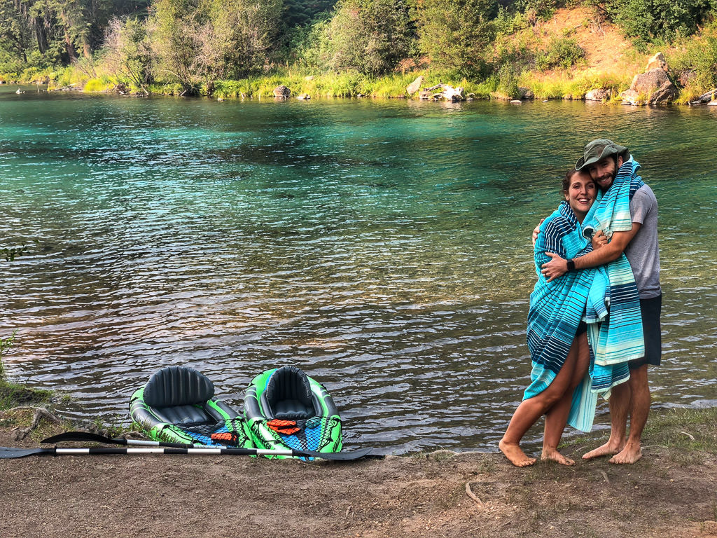 Young couple poses for picture with their inflatable kayaks on the shore of a lake