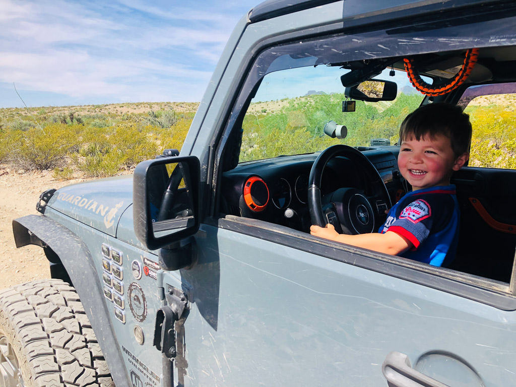 Little boy smiling out the driver side window of parked Jeep.