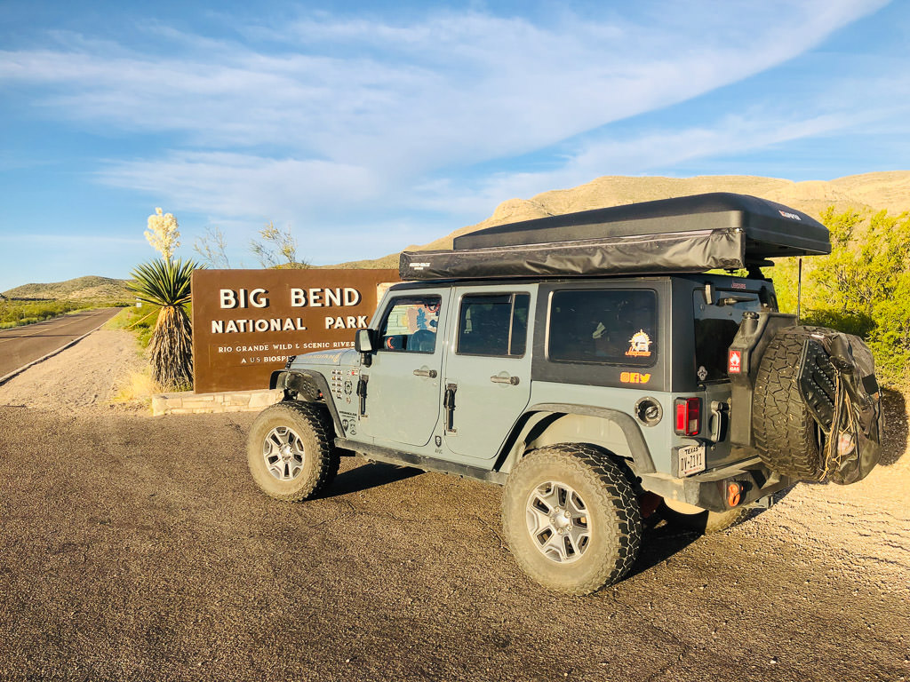 Jeep parked in front of sign for Big Bend National Park.