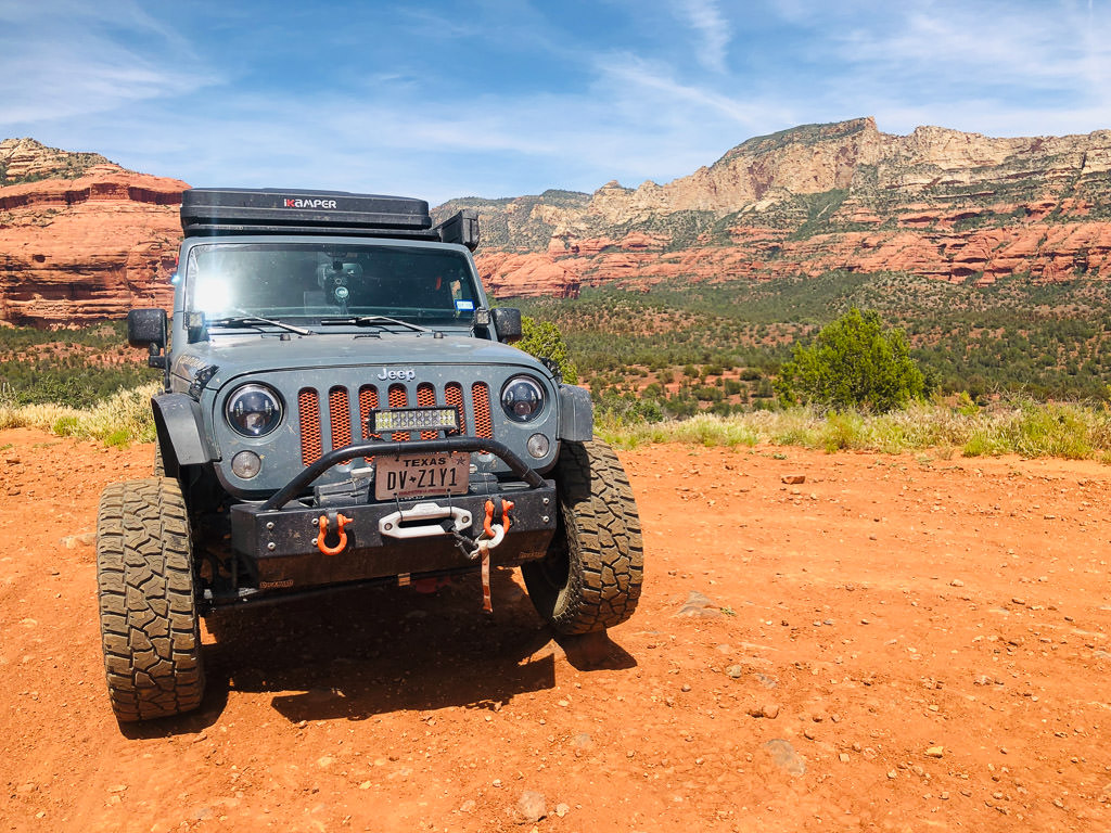 Jeep with red rock formations in the background.