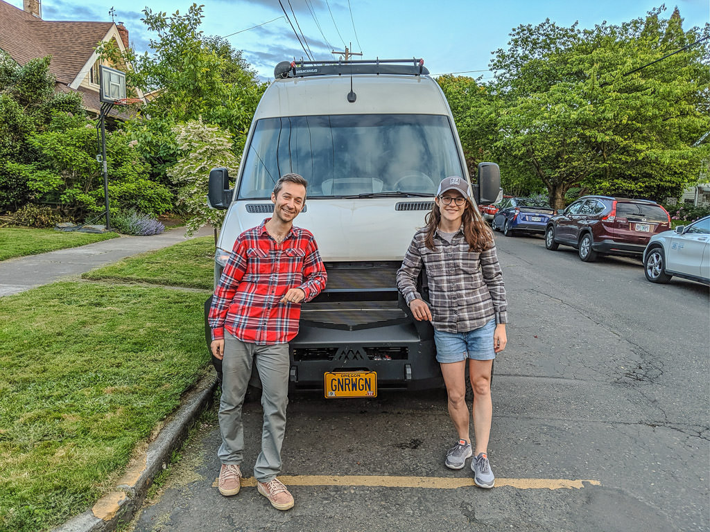 Young couple poses in front of their Winnebago Revel