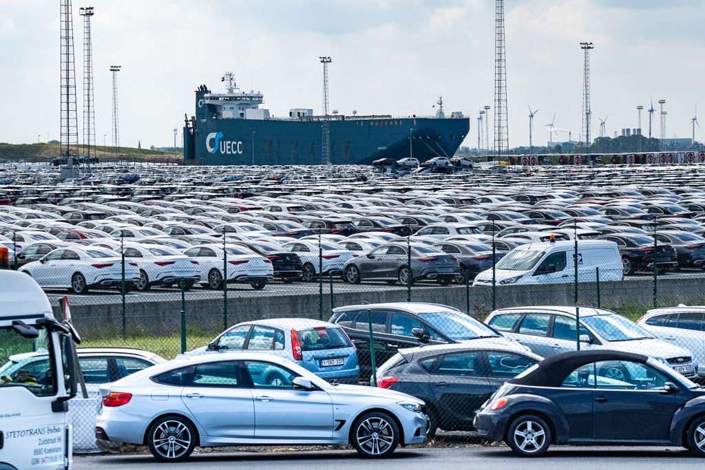 Parking lots full of cars waiting to be loaded onto a freighter.