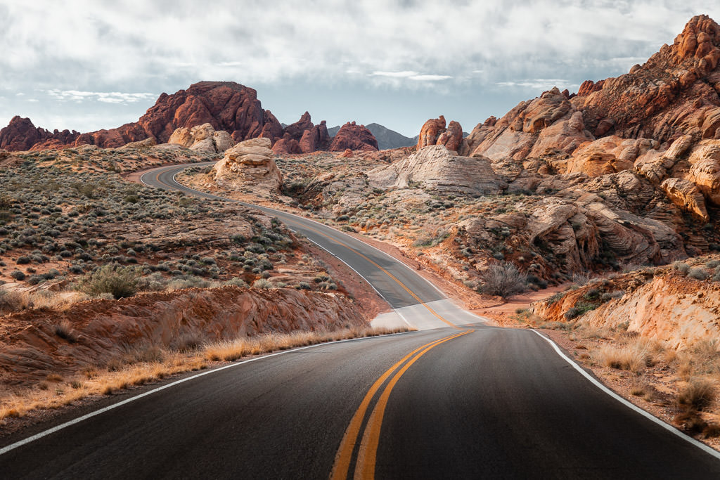 Empty road winding along the edge of Red Rock Canyon.